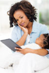 mother looking at iPad for breastfeeding help while holding her sleeping baby