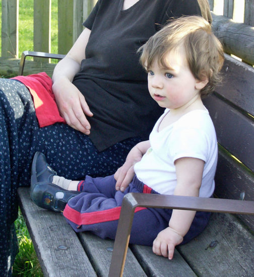 Mother sits on bench with toddler
