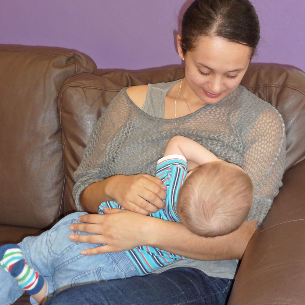 mother breastfeeding older baby in cradle hold