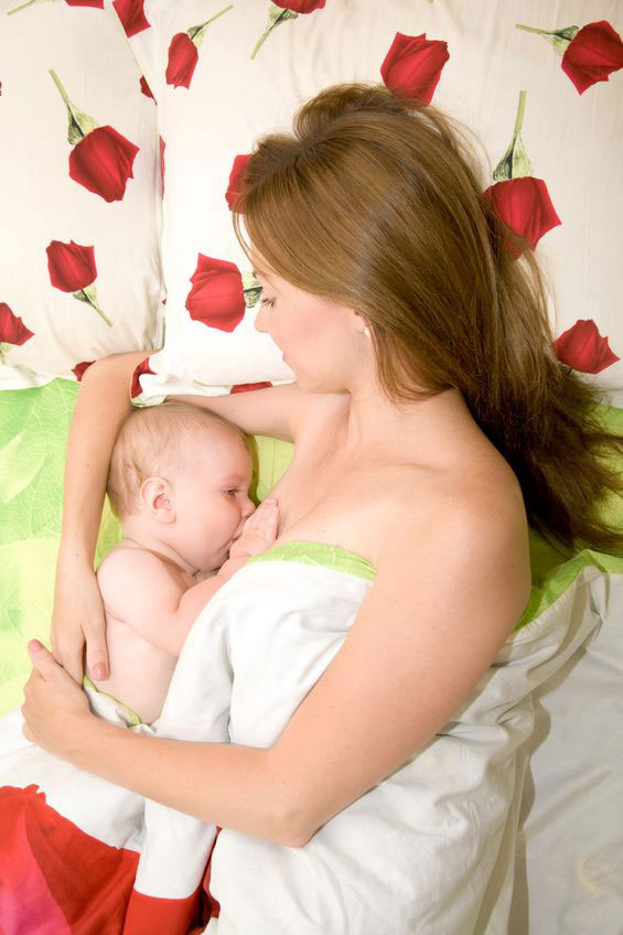mother lies on bed to breastfeed