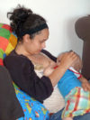 mother holding baby to breastfeed in a reclining straddle hold