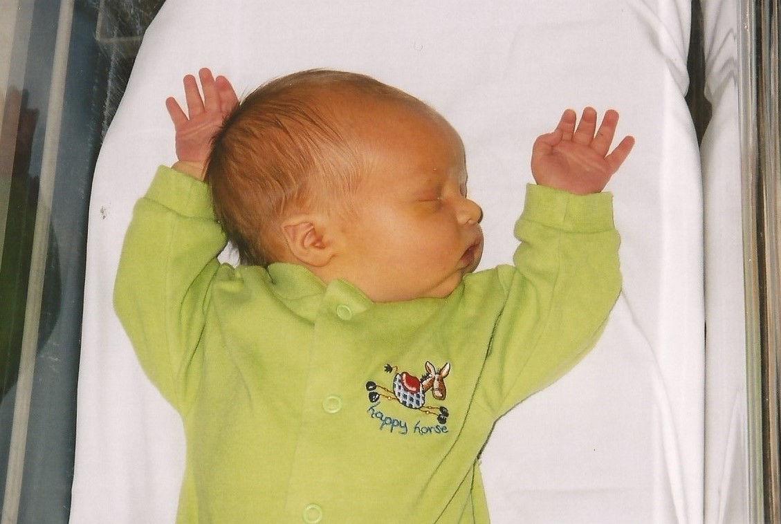 Jaundiced baby asleep in a pram with a green babygro