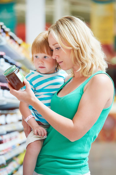 Mother checks labels in supermarket holding toddler
