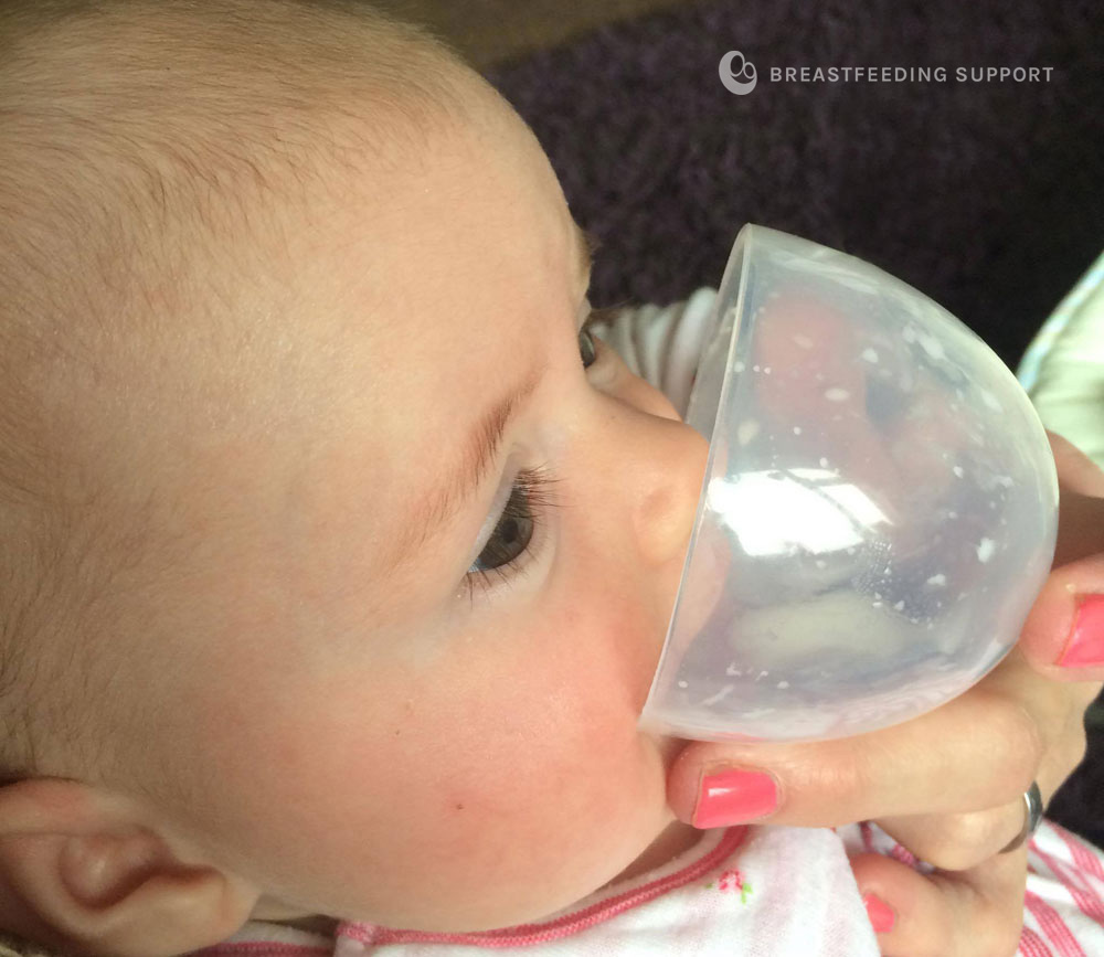 Baby drinking from a little cup