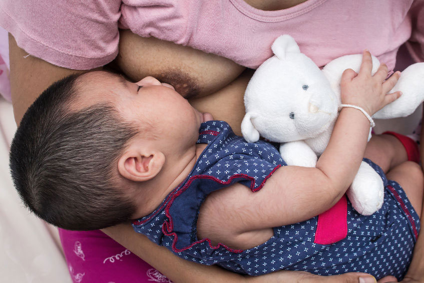 mother breastfeeding baby holding a teddy