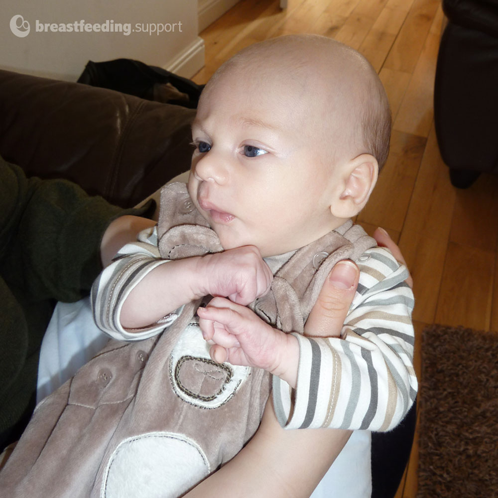 A hungry baby, with tight fists, a frown and bent elbows