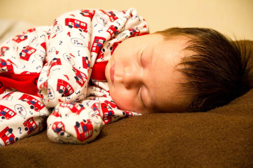 Les mains de bébé sont couvertes de mitaines à gratter intégrées dans le survêtement